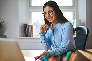 Smiling woman working at home office on laptop
