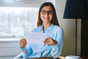 Happy woman in glasses holding envelope