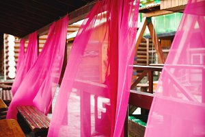 Bright pink curtains in street cafe