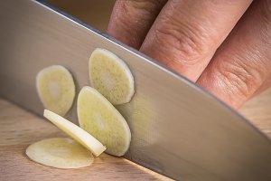 Chef slicing garlic cloves