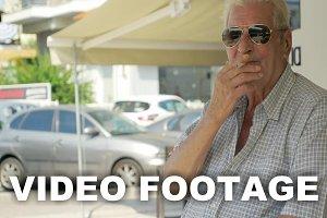 Smoking senior man in the street