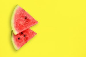 Watermelon slices on yellow table