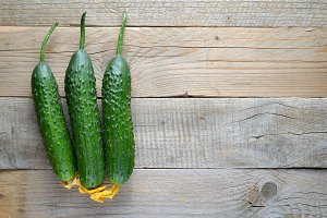 Cucumbers on wooden table top view