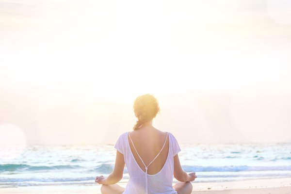 woman practicing yoga at sunrise be…