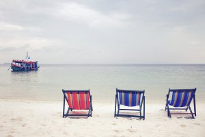 Three deck chairs on the beach