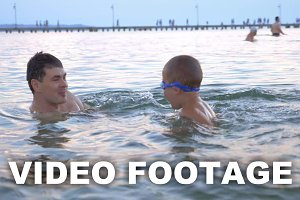 Boy Swimming in the Sea with Parents