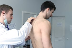 Doctor examining back of young male patient with stethoscope