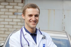 Portrait of young caucasian medical doctor smiling outdoor