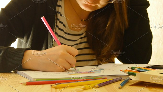 Young woman holds a pencil and draws at home. Coloring for adults and children. For stress relief. Adult coloring - People