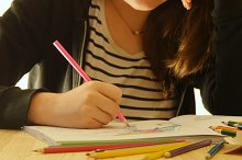 Young woman holds a pencil and draws at home. Coloring for adults and children. For stress relief. Adult coloring book