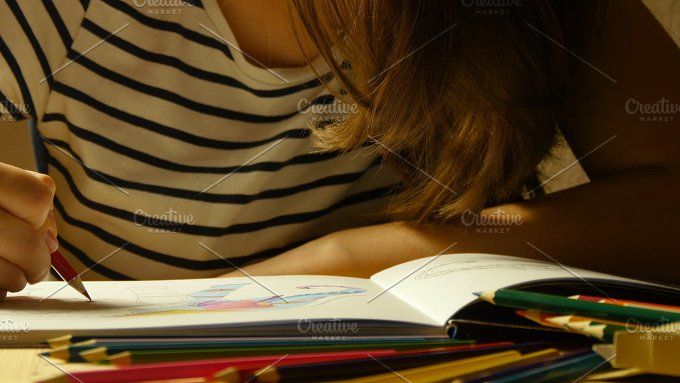 Attractive girl in glasses draws coloring book. Close up - Arts & Entertainment