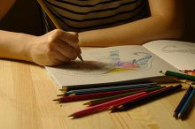 Female hands draws adult coloring book late night. Close up