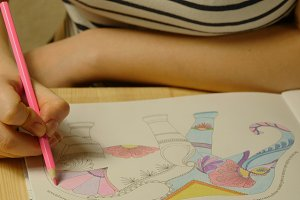 Woman draws coloring for adults and children at home.