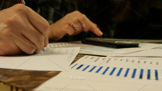 Hands of businessman and businesswoman.New charts and graphs appear on the table - Business