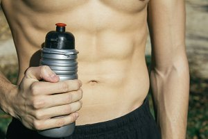 Fit man holding a bottle