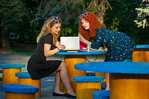 Girlfriends in park with a laptop