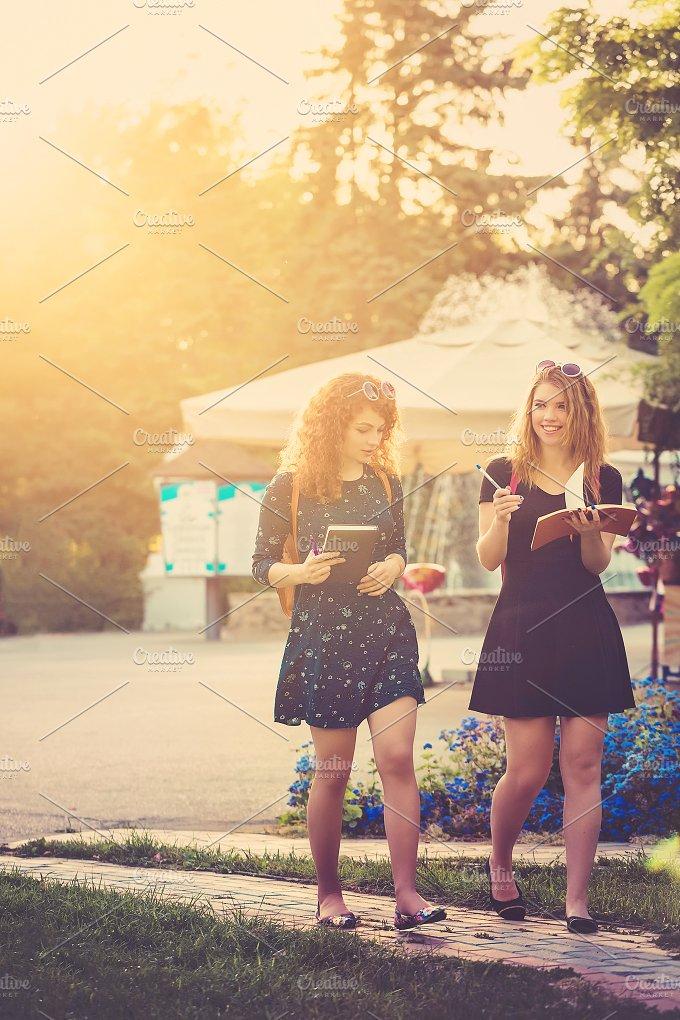 Girlfriends walking in park. BFF - Education
