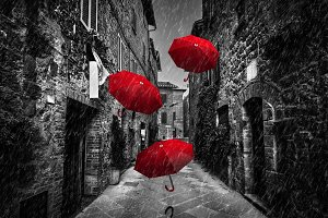 Red umbrellas flying with wind.