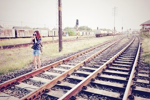A woman taking photos at a railway