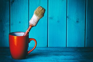 Old paint brush in red cup