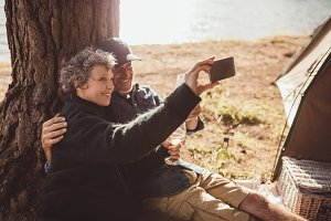 Mature couple camping near a lake