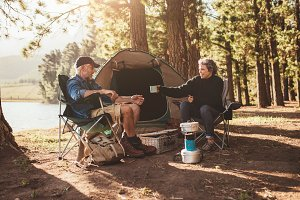 Senior couple camping by a lake