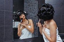 Girl doing makeup in bathroom.