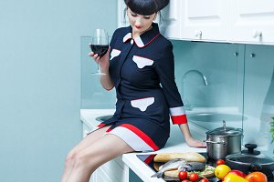 Girl is drinking wine in kitchen.