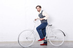 Man in vest holding a bicycle.