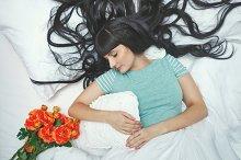 Girl asleep in bed. Flowers.