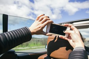 Hands taking a selfie photo in a car