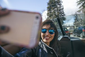 Woman taking a selfie photo in a car
