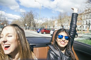 Women having fun in a cabriolet car
