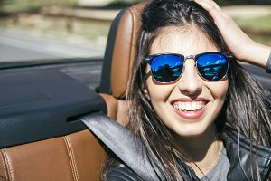 Woman with sunglasses smiling in car
