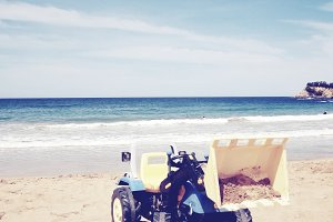 A dozer toy dumping sand on a beach