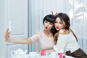 Girlfriends doing selfie. Tea party.