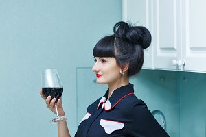 Girl drinking aperitif in kitchen.