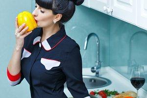 Girl kisses pepper. In the kitchen.