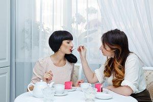Girlfriends drink tea with cake.
