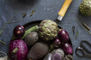 Purple fruits and vegetables on a black background