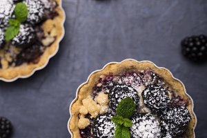 Small tarts with blackberries on a dark background