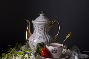 Still life of tea in a porcelain bowl with strawberries