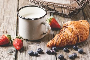 Croissant, milk and berries
