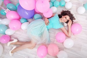 Happy girl lying among balloons.
