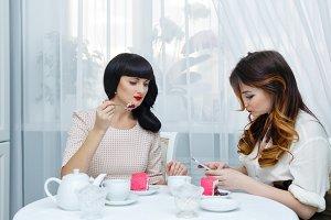 Girlfriends drink tea with cake
