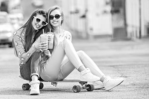 Beautiful young girls hipster girlfriends posing with a skateboard seat on skate, street fashion lifestyle in sunglasses