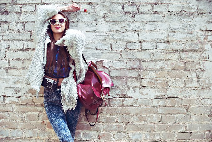 Young street fashion girl on the background of old brick wall. Outdoors, lifestyle. - People