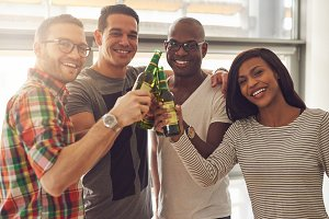Four smiling friends tapping beer bottles