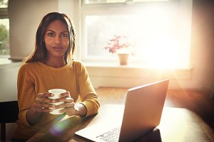 Serious woman holding coffee near open laptop