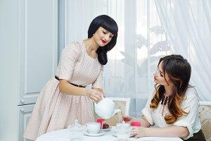 Woman pours tea girlfriend.